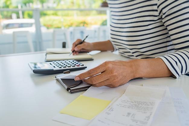 Femme, factures, calculatrice femme à l'aide d'une calculatrice pour calculer les factures à la table au bureau. calcul des coûts. Photo Premium