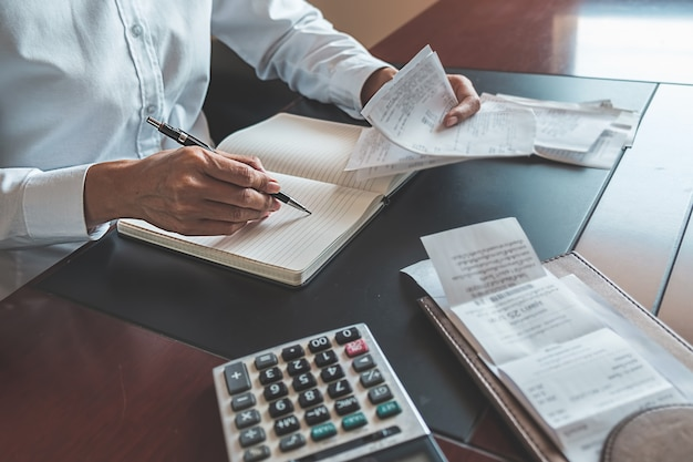 Femme, factures, calculatrice femme à l'aide d'une calculatrice pour calculer les factures à la table au bureau. Photo Premium