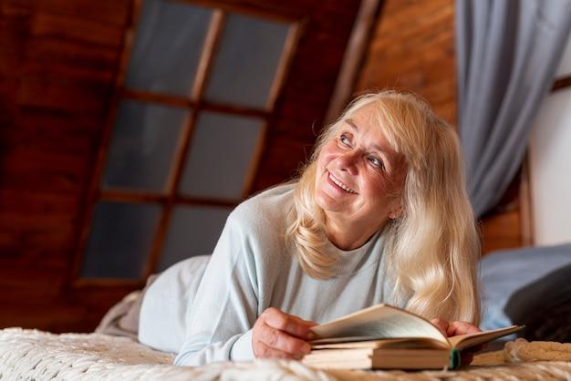 Femme faible angle à la maison lecture Photo gratuit