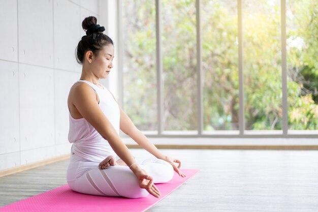 Femme, Faire, Yoga, Exercice, Intérieur, Gymnase Concept De Bonne Santé Et De Bien-être. Photo Premium