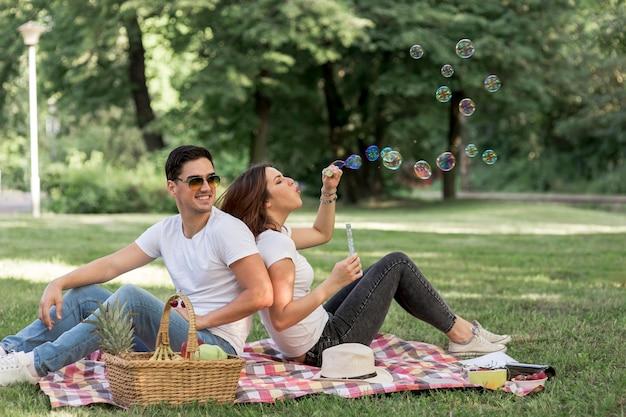 Femme faisant des bulles au pique-nique Photo gratuit