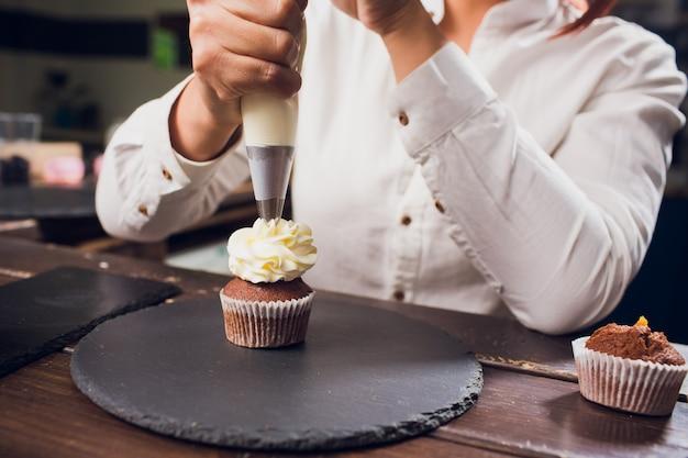 Femme Faisant Du Fromage à La Crème Sur Des Cupcakes Dans La Cuisine. Gâteaux De Cuisine. Photo Premium