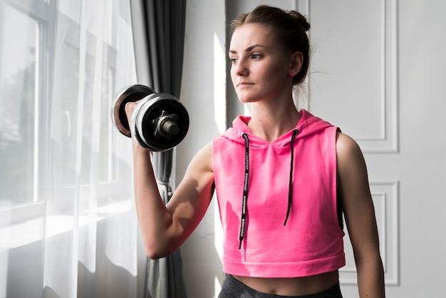 Femme faisant de l'exercice avec haltère à la maison Photo gratuit