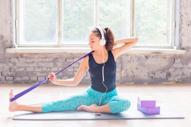 Femme faisant de l'exercice avec une sangle de yoga sur un tapis d'exercice Photo gratuit