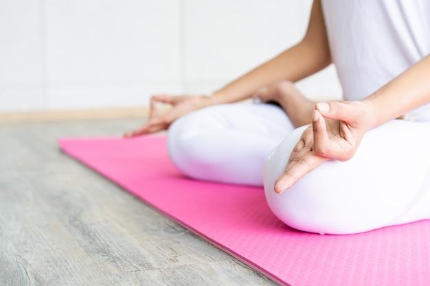 Femme Faisant Des Exercices De Yoga Dans La Salle De Sport Couverte Se Bouchent Avec La Surface. Photo Premium
