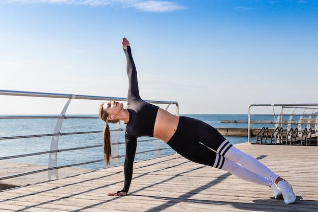 Femme faisant des exercices de yoga de platelage Photo Premium