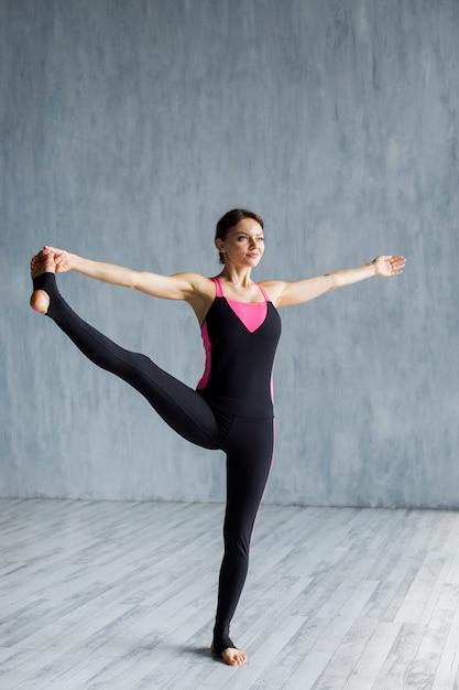 Femme faisant une extension de jambe latérale Photo gratuit