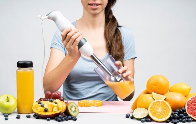 Femme faisant un jus d'orange Photo gratuit