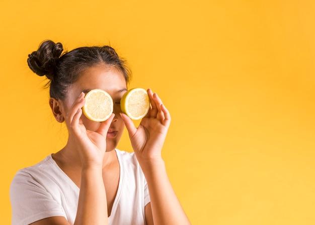 Femme faisant des lunettes de soleil à partir de moitiés de citron Photo gratuit