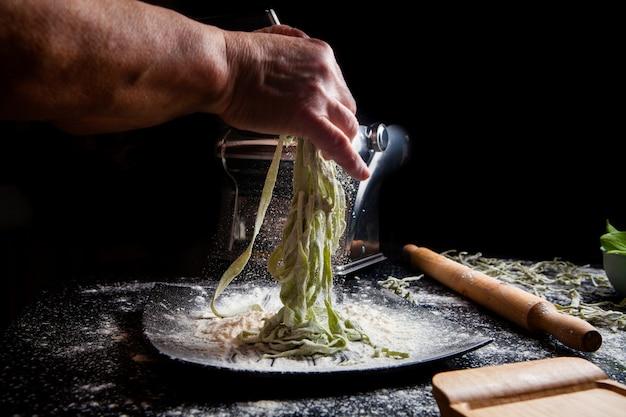 Femme Faisant Des Pâtes En Plaque Avec Des Ustensiles De Cuisine Sur Fond Noir. Vue Latérale Horizontale Photo gratuit