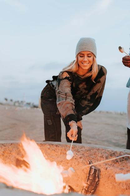Femme faisant rôtir une guimauve sur un feu de joie Photo Premium