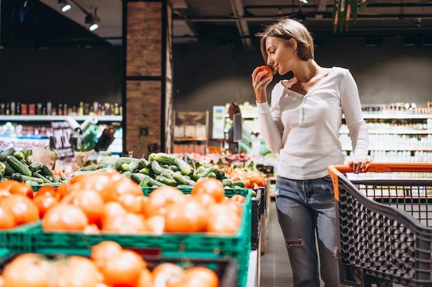 Femme faisant ses courses à l'épicerie Photo gratuit
