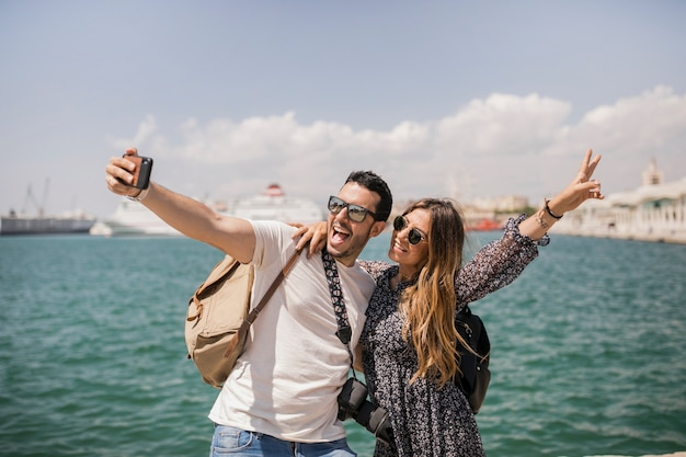 Femme faisant signe de paix avec son petit ami prenant selfie sur mobile Photo gratuit