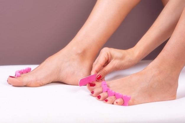 Femme faisant des soins des pieds et des ongles. Photo Premium