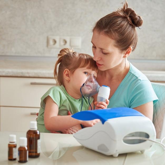 Femme fait l'inhalation à un enfant à la maison Photo Premium