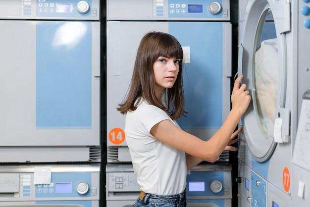 Femme Fermant La Porte De La Machine à Laver Photo gratuit