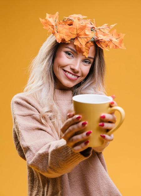 Femme, à, feuilles érable, diadème, projection, tasse, café, debout, contre, mur jaune Photo gratuit