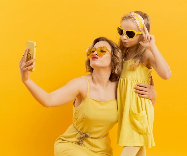 Femme Et Fille Prenant Un Selfie Tout En Portant Des Lunettes De Soleil Photo gratuit