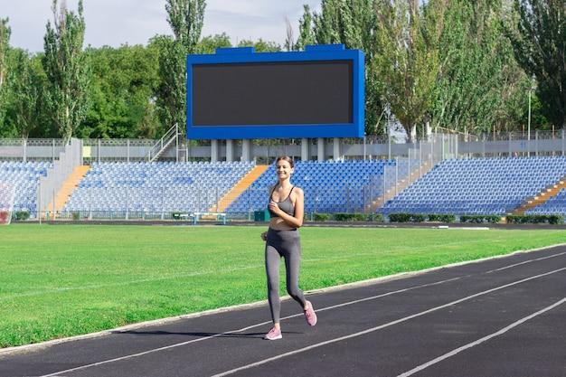 Femme de fitness en cours d'exécution sur piste dans le stade. entraînement en été. Photo Premium