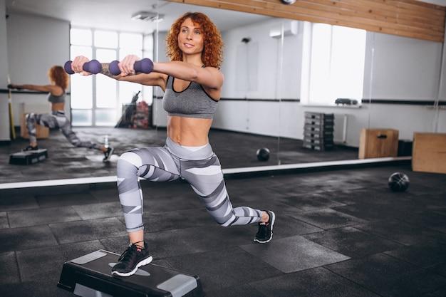 Femme fitness faisant des mouvements brusques avec des haltères au gymnase Photo gratuit