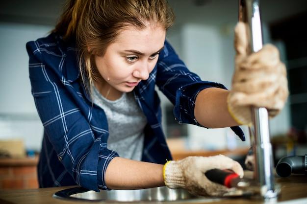 Femme fixant un évier de cuisine Photo Premium