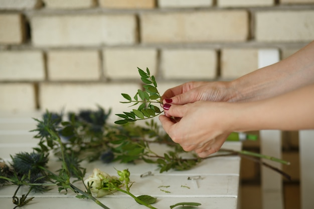Femme fleuriste recueille le bouqet d'une fleur fraîche Photo Premium