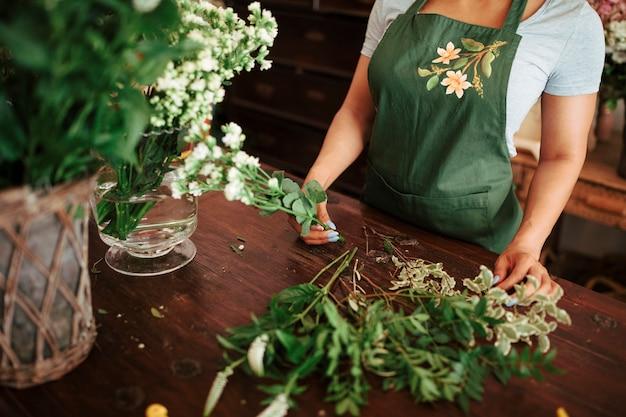 Femme, fleuriste, tenue, bouquet, de, blanc frais, fleurs, sur, bois, bureau Photo gratuit