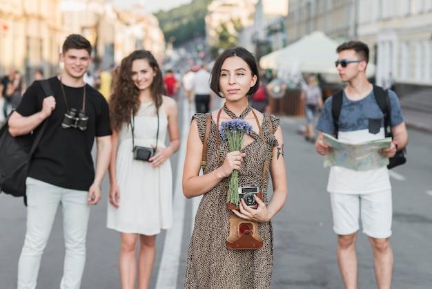 Femme avec des fleurs et de la caméra, explorer la ville avec des amis Photo gratuit