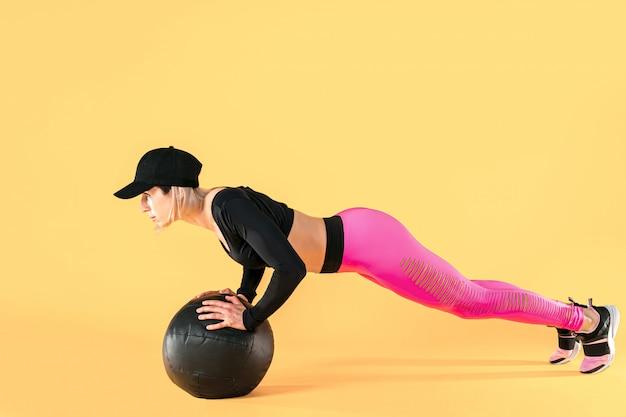 Femme En Formation De Vêtements De Fitness Avec Un Médecine-ball. Athlète Féminine Faisant L'entraînement De L'abdomen à L'aide D'un Médecine-ball. Photo Premium