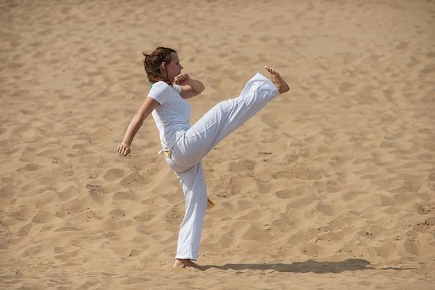 Femme forme la capoeira en plein air. fille effectue un coup de pied Photo Premium