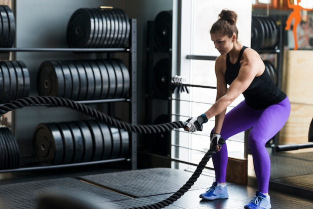Femme forte exerçant avec des cordes Photo gratuit