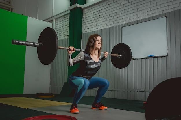 Femme forte, soulevant des haltères dans le cadre de l'exercice de crossfit Photo Premium