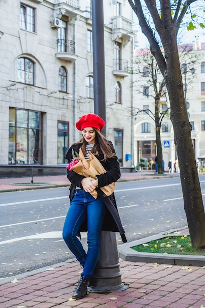 Femme française avec des baguettes dans la rue en béret Photo gratuit
