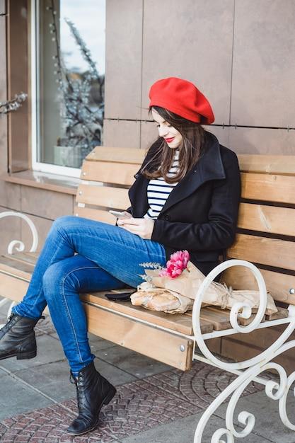 Femme Française Dans Un Béret Rouge Sur Un Banc De Rue Photo gratuit