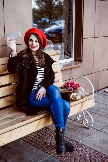 femme fran aise dans un b ret rouge sur un banc de rue. Black Bedroom Furniture Sets. Home Design Ideas