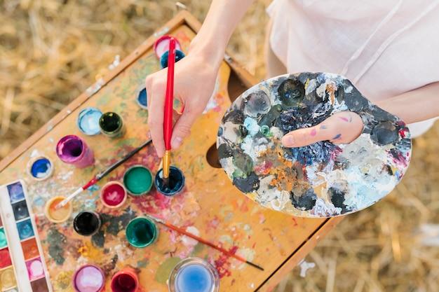 Femme grand angle avec des éléments de peinture Photo gratuit