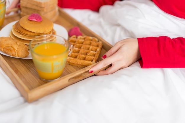 Femme grand angle servant le petit déjeuner au lit Photo gratuit