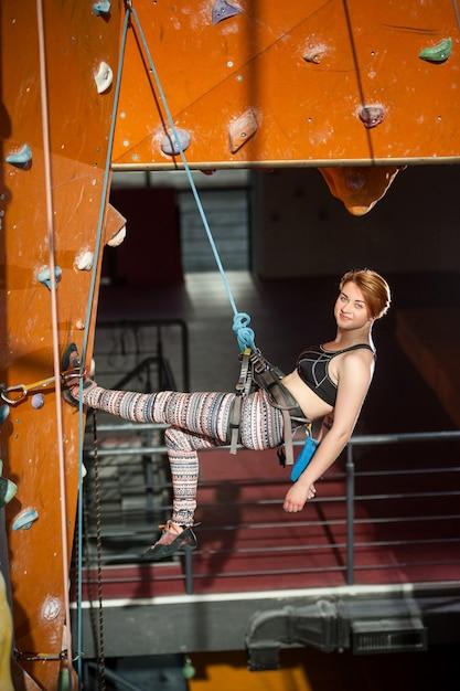 Femme grimpante grimpe sur un mur d'escalade intérieur Photo Premium