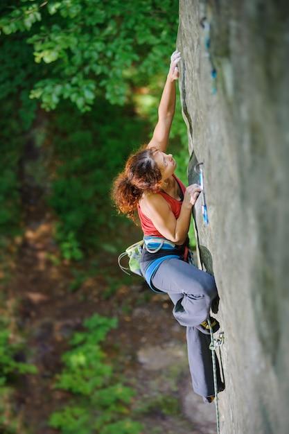 Femme, grimpeur, à la recherche de la prochaine adhérence sur une paroi rocheuse difficile en altitude avec corde Photo Premium