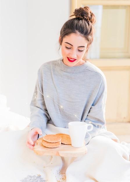 Femme en gris assis avec des biscuits Photo gratuit