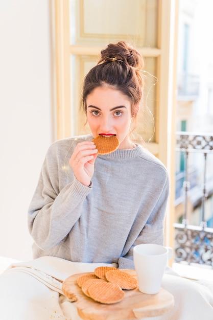 Femme, gris, manger, biscuits Photo gratuit