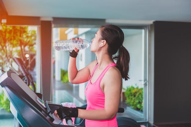 Femme de gym travaillant l'eau potable par des machines de fitness moonwalker. modèle de fitness féminin asiatique insi Photo Premium