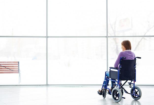 Femme handicapée en regardant la fenêtre Photo gratuit