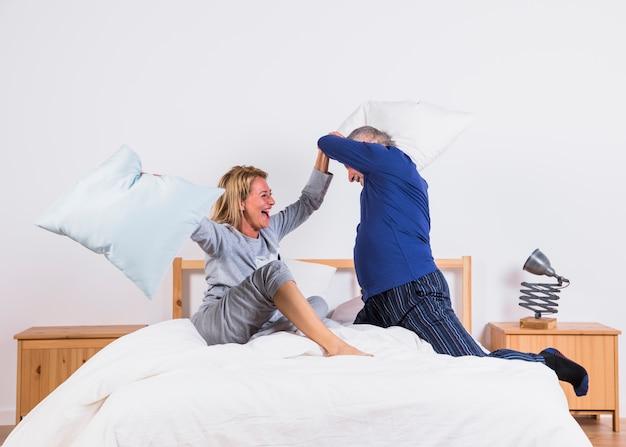 Femme heureuse âgée et homme avec des oreillers s'amusant sur le lit dans la chambre Photo gratuit