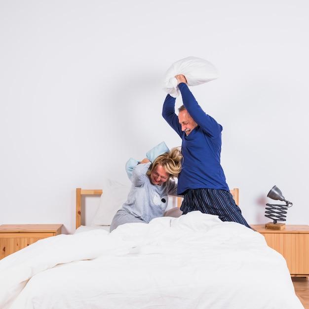 Femme heureuse âgée et homme avec des oreillers s'amusant sur le lit Photo gratuit