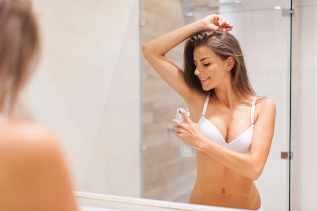 Femme Heureuse à L'aide De Déodorant Sous Les Aisselles Photo gratuit