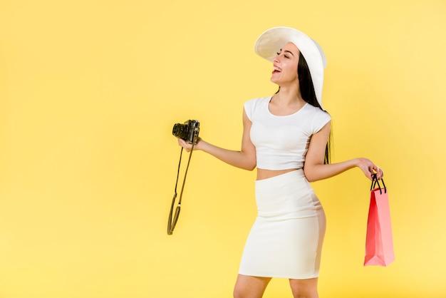 Femme heureuse avec appareil photo et sac rose Photo gratuit