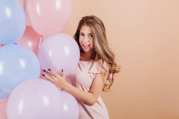 Femme Heureuse Aux Longs Cheveux Ondulés Posant Avec Des Ballons D'hélium Colorés Photo gratuit