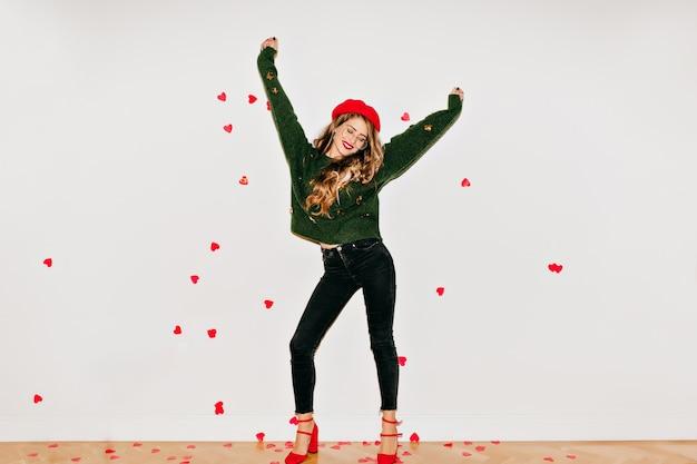 Femme Heureuse En Chaussures à Talons Hauts Rouges Dansant Sur Un Mur Blanc Sous Des Confettis Coeur Photo gratuit