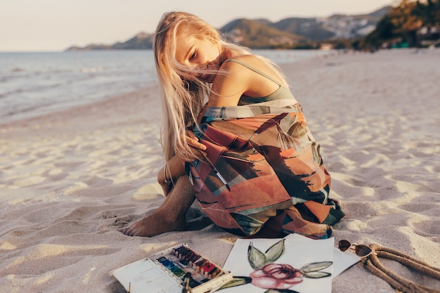 Femme Heureuse Avec Des Cheveux Blonds Venteux Assis Sur Le Sable, à La Recherche Sur Son Aquarelle Photo gratuit
